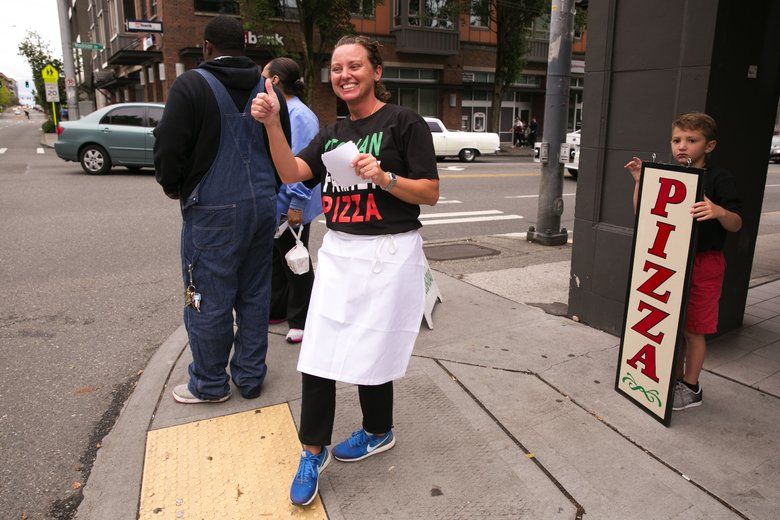 Jennifer Calozzi and her younger son Sal drum up business outside their restaurant Italian Family Pizza, which recently relocated to First Hill.  (Erika Schultz/The Seattle Times)