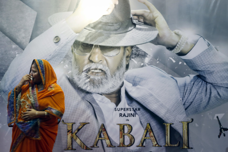 A movie-goer stands in front of Kabali's movie poster at a cinema in Kuala Lumpur, Malaysia, Thursday, July 21, 2016. The movie starring Indian actor Rajinikanth opens worldwide tomorrow, July 22. (AP Photo/Joshua Paul)