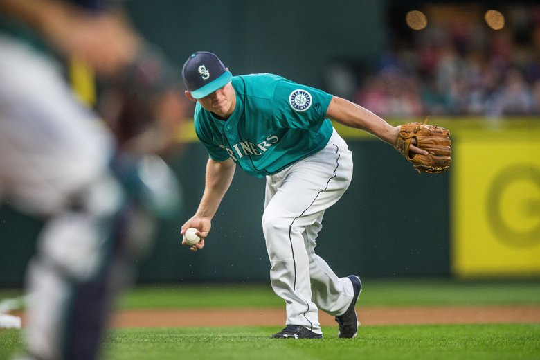 Kyle Seager barehands the infield grounder off Milwaukee's Jonathan Villar on Aug. 19.  (Dean Rutz / The Seattle Times)