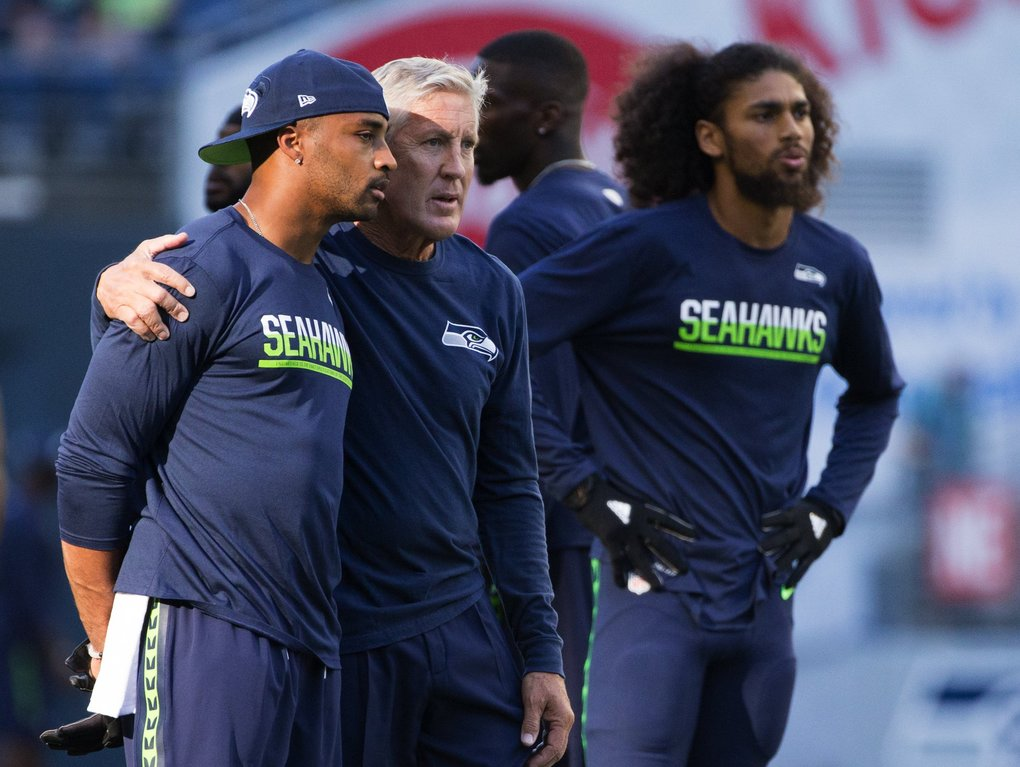 Seahawks wide receiver Doug Baldwin talks with Seahawks Head Coach Pete Carroll before a preseason game between the Seahawks and the Cowboys at CenturyLink Field.  (Lindsey Wasson / The Seattle Times)