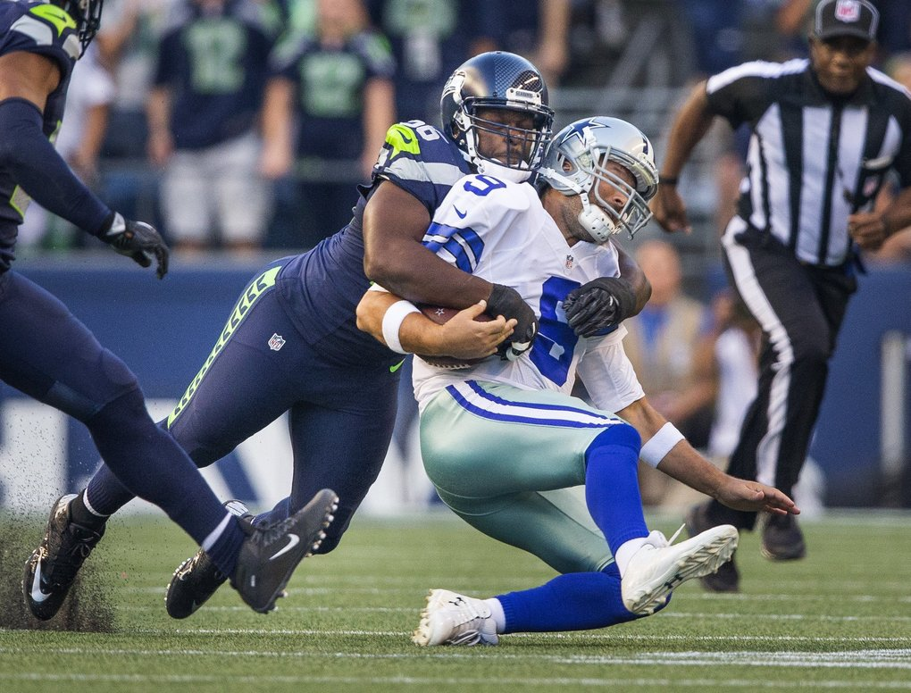 Cliff Avril knocks Dallas quarterback Tony Romo out of the game with this sack on the second play of the game Thursday.   (Dean Rutz / The Seattle Times)