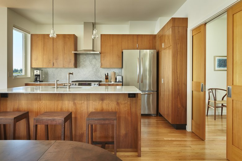 The open, inverted design sites the living and dining areas and the kitchen on the upper level. The cabinets are walnut, with Carrara marble countertops and white oak floors. (Benjamin Benschneider/The Seattle Times)