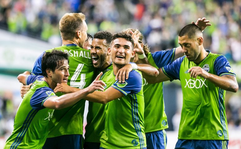 The Sounders celebrate scoring their third goal of the second half as midfielder Cristian Roldan, front middle, put the exclamation point on the team's 3-1 win over Cascadia Cup rival Portland last August. (Bettina Hansen/The Seattle Times)