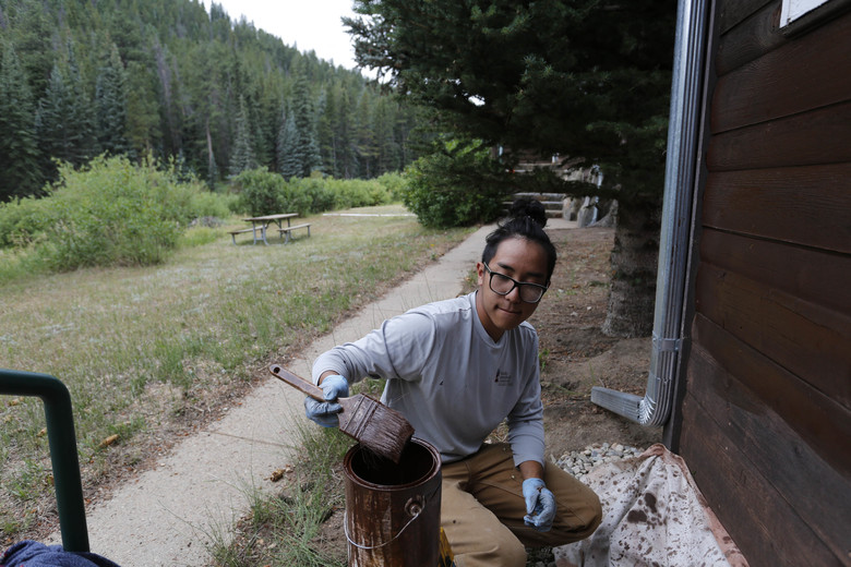 Adam Nguyen, a crew member for the non-profit organization Rocky Mountain Conservancy, helps restore old cabins used by research scientists inside Rocky Mountain National Park, near Estes Park, Colo., on Aug. 4, 2016. Rocky Mountain Conservancy works for the U.S. Park Service, running crews who do whatever work is needed. (AP Photo/Brennan Linsley)