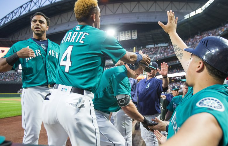 Kyle Seager is welcomed to the dugout after his solo home run in the 4th inning. (Dean Rutz/The Seattle Times)