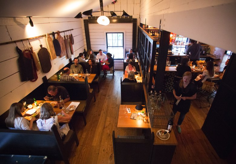 Whitewashed plank walls and butcher-block surfaces update the original structure, built in the 1850s. Cozy booths line the rear dining room, adjacent to a four-seat bar seen at right.  (Lindsey Wasson/The Seattle Times)