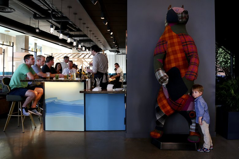 Owen Ozol, 4, from Walnut Creek, Calif., stops to hug the plaid bear statue that greets customers at Scout.  (Johnny Andrews/The Seattle Times)