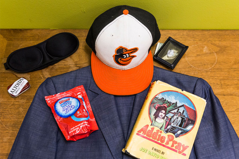 "A Baltimore Orioles cap, a cherished novel and other common carry-on items toted by Derek Waters, the co-creator of Comedy Central's ""Drunk History."" (Emily Berl/The New York Times)"