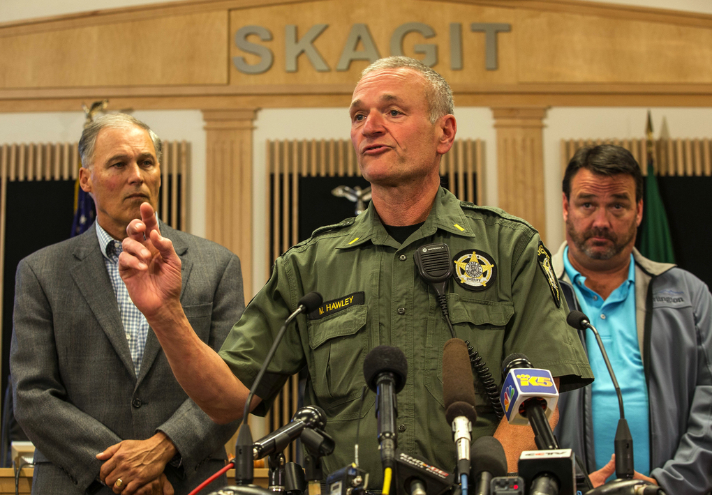 Lt. Mike Hawley with Island County Sheriff's office discusses the capture of Arcan Cetin, 20, who was wanted in connection with Friday's mass shooting at Cascade Mall in Burlington on Friday.  Officials, including Washington Gov. Jay Inslee, left, gathered in the Skagit County chambers in Mt. Vernon on Saturday.   (Dean Rutz / The Seattle Times)