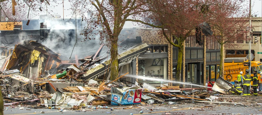 Seattle firefighters douse hot spots after the explosion last March flattened buildings on Greenwood Avenue North. Nine firefighters were hurt when a natural-gas leak sparked the blast.  (Mike Siegel/The Seattle Times)