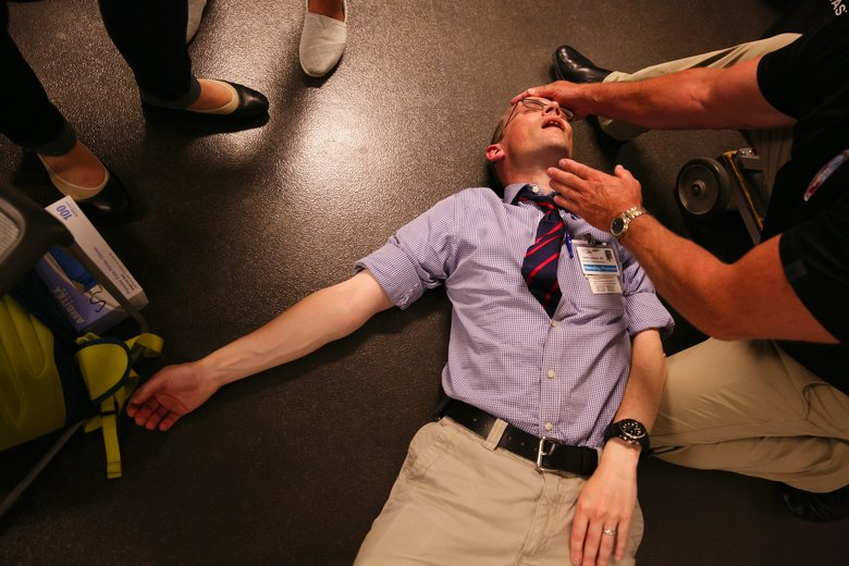 Dr. David Carlbom, of the Harborview Paramedic Training Program, on floor, poses as an unresponsive victim of an airway obstruction during the first-day session with new UW medical students. He was assisting clinical educator Mike Helbock, of the UW School of Medicine. (Erika Schultz/The Seattle Times)