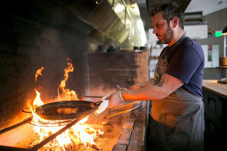 """From this point, the paella needs to be always at boiling temperature,"" says chef Perfecte Rocher at Tarsan i Jane. (Johnny Andrews/The Seattle Times)"
