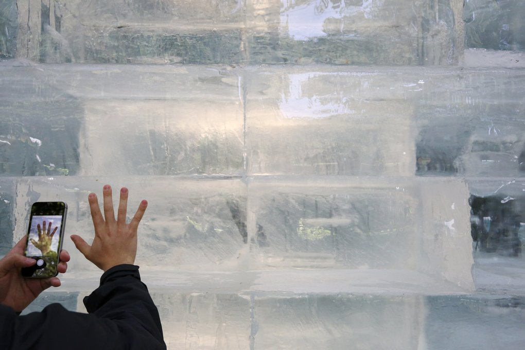 The cube of ice becomes a background pattern for many placing their hands on the sculpture. (Alan Berner/The Seattle Times)