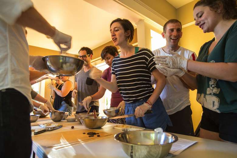It's all hands on deck for a chocolate-making class at Moishe House, which helps young Jewish professionals connect and socialize in Seattle. Among the organizers is Nathan Wasserman, center, in white T-shirt.  (Dean Rutz/The Seattle Times)