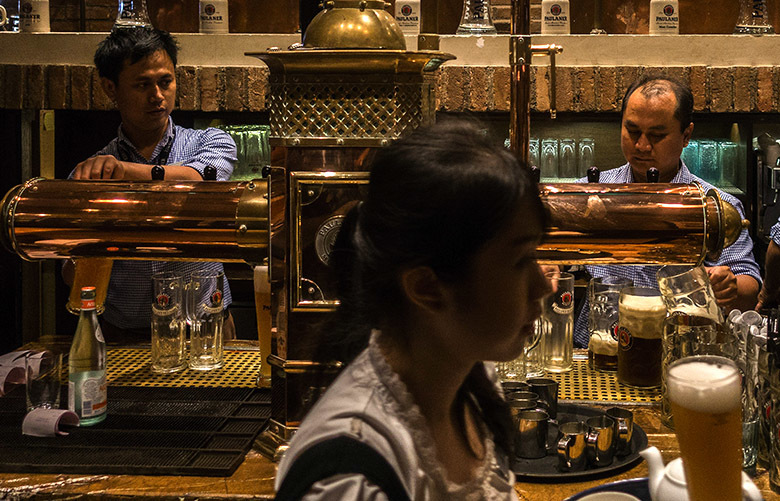 Bartenders fill beer steins at a german bar and restaurant in Jakarta, Indonesia, Aug. 6, 2016. Indonesia's Islamic political parties have repeatedly attempted to pass alcohol bans with little success in this secular, multi-faith society, but a new line — that it should be done for health reasons, not religious reasons — is gaining traction. (Kemal Jufri/The New York Times)