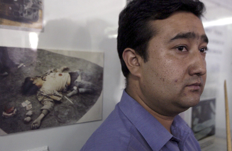 FILE – In this Sept. 15, 2003, file photo, a Uighur official stands near a picture of a dead separatist militant at an exhibition in Hotan in China's western Xinjiang province. Since 2015 militants belonging to the Uighur ethnic group native to the vast Xinjiang region in western China have shown signs of becoming a force in Islamic extremism globally, a development that is reshaping both the ground war in Syria and Chinese foreign policy. (AP Photo/Ng Han Guan, File)