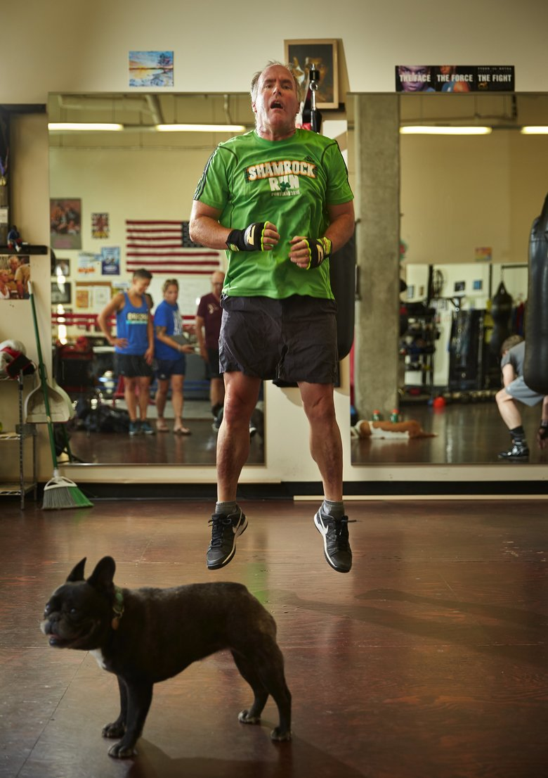 Peter Hussey does jumping drills as Chloe, a French bulldog who belongs to one of the coaches, stands by. The class works with people who are affected with Parkinson's.  (Benjamin Benschneider/The Seattle Times)