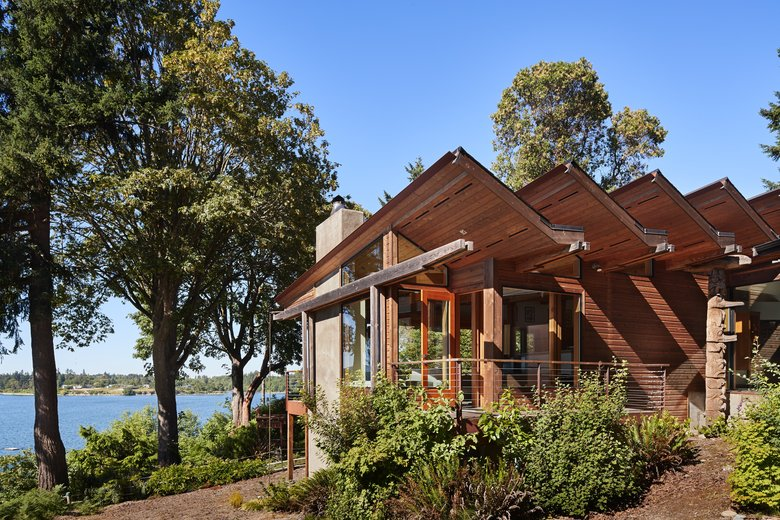 """Architect Bob Swain responded to the coastal setting of Alan and Jan Frost's Maury Island home (built by Cascade Pacific Construction) with """"exotic forms"""" and """"sweeping 'waves' of monitors and clerestories."""" All the monitors drain to one point to the northwest, he says, and a separate connecting roof transitions to a reflecting pool. (Benjamin Benschneider/The Seattle Times)"""