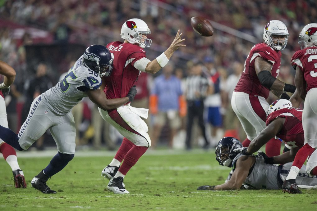 Seattle Seahawks defensive end Cliff Avril (56) gets to Arizona Cardinals quarterback Carson Palmer (3) in the second quarter. (Dean Rutz / The Seattle Times)