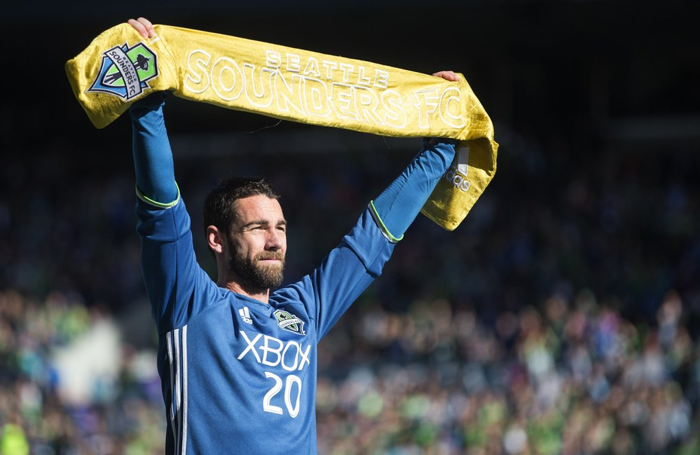 "Seattle Sounders defender Zach Scott, nicknamed ""Mr. Sounder,"" holds up the Golden Scarf presented to him before the game. (Lindsey Wasson / The Seattle Times)"