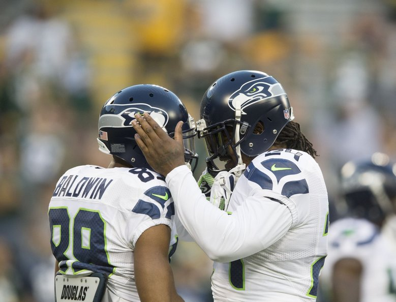 Seahawks running back Marshawn Lynch, right, and receiver Doug Baldwin share a moment during a game against the Packers on Sept. 20, 2015, at Lambeau Field. Green Bay won 27-17. (Dean Rutz / The Seattle Times)