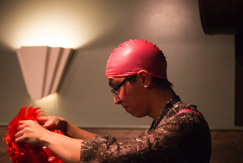 Vincent Chen prepares to don a bright red wig in the makeup room. (Lindsey Wasson / The Seattle Times)