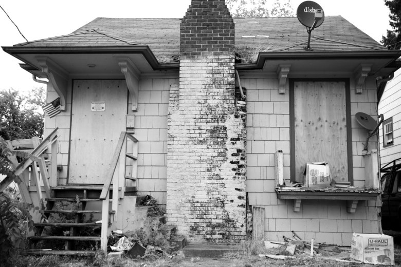 Many houses in the neighborhood near Roosevelt High School are vacant and boarded up. (Ken Lambert/The Seattle Times)