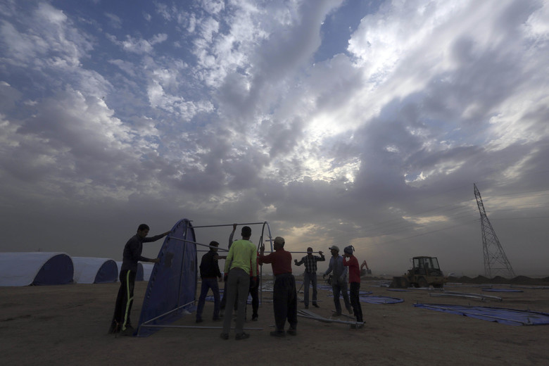 Workers set up a camp for displaced Iraqis in Khazer, Iraq, Wednesday, Oct. 19, 2016. More than 25,000 troops have mobilized for the Mosul fight, a massive operation that's expected to take weeks, if not months. Mosul is Iraq's second largest city and the largest urban area controlled by the Islamic State militants. (AP Photo/Khalid Mohammed)