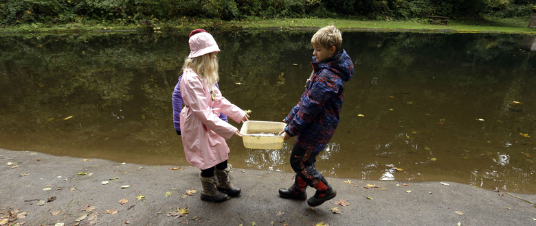 In this Oct. 6, 2016 photo, Outdoor School students Maya Herring, left, and Karl Krueger carry a bucket full of pond water to be studied during a lesson at Camp Howard in Mount Hood National Forest near Corbett, Ore. The outdoor education is unique to Oregon and is a rite-of-passage for public school students that's meant to instill a respect for nature in each generation – studies show it improves attendance and boosts test scores. (AP Photo/Don Ryan)