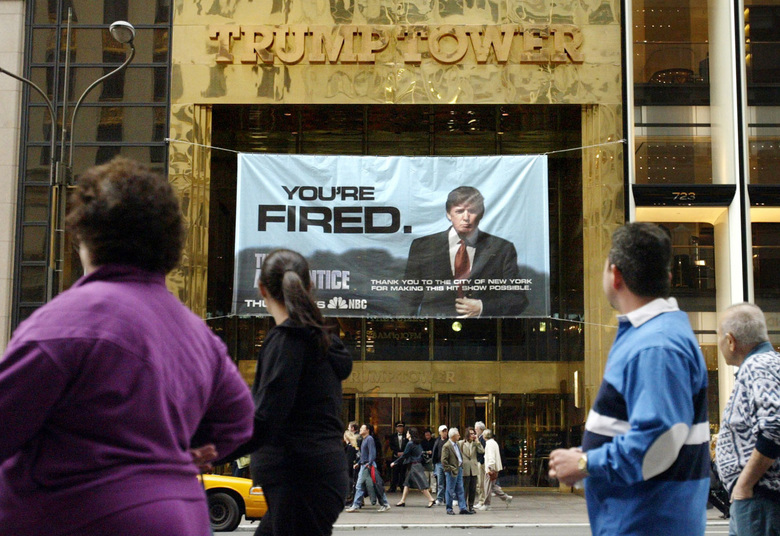 "FILE – In this Saturday, March 27, 2004 file photo, passersby look at a sign advertising the reality television show, ""The Apprentice,"" displayed at the entrance to the Trump Tower building in New York. Donald Trump's development firm was issued summonses by the city because it did not have the proper permits for the giant banner. In his years on the show, Trump repeatedly demeaned women with sexist language, according to show insiders who said he rated female contestants by the size of their breasts and talked about which ones he'd like to have sex with. (AP Photo/Bebeto Matthews)"