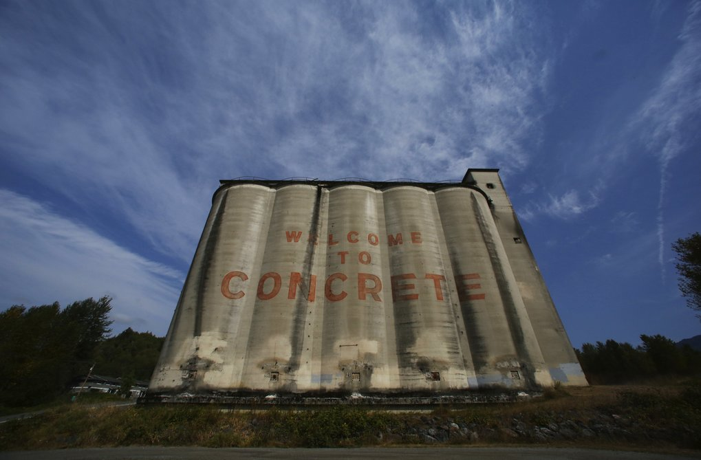 "That Giant Concrete Thing along Highway 20 in the town of Concrete once was something far more functional than just a welcome sign: It's actually a cluster of five massive cement silos — the largest surviving remnant of two former cement factories on either side of the Baker River in the town renamed to honor its long-ago chief export. Cement made with limestone from nearby quarries during the first half of the 20th century helped build the Grand Coulee Dam and Ballard Locks. The ""Welcome"" wording is not original; it was added to the nine-story behemoth during the 1992 filming of the movie ""This Boy's Life.""  (Alan Berner/The Seattle Times)"