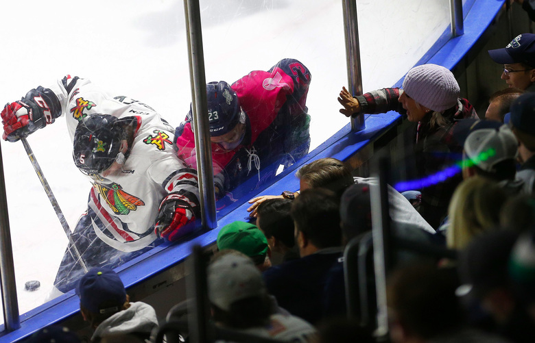 A woman bangs on the glass as Seattle Thunderbirds right wing Luke Ormsby (23) and Portland Winterhawks defenseman Matthew Quigley (5) fight for the puck. (Logan Riely/The Seattle Times)