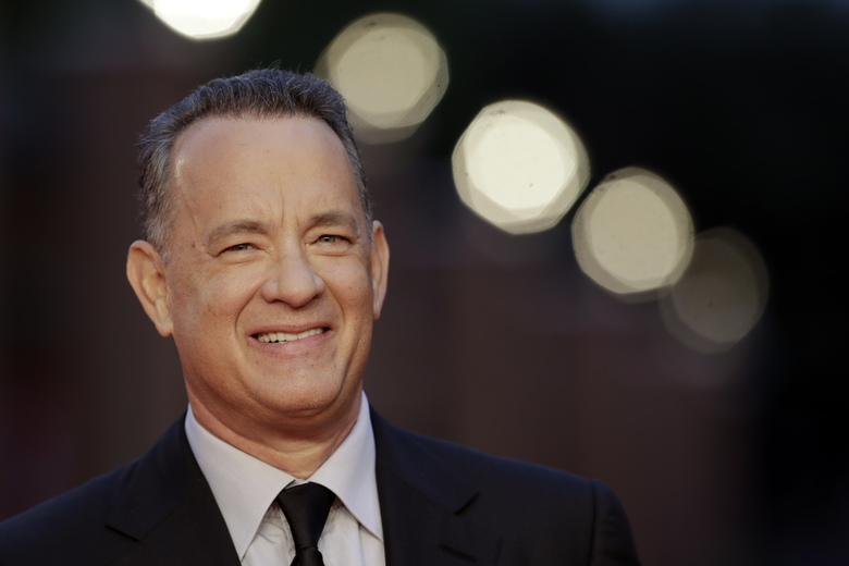 "FILE – In this Thursday, Oct. 13, 2016 file photo, actor Tom Hanks arrives to receive a lifetime achievement at the Rome Film Festival, in Rome. Within the manic action of ""Inferno,"" the latest big-screen adaptation of a Dan Brown thriller, is a warning about the dangers of seeking simple solutions to complex problems. Star Tom Hanks says it's a theme with echoes in the current U.S. presidential race. ""Inferno"" sets Hank's polymathic professor Robert Langdon on the trail of a deadly plague concocted by billionaire scientist Bertrand Zobrist (Ben Foster) out of a sort of warped humanitarianism: He plans to end war, poverty and famine by wiping out half the world's population. (AP Photo/Andrew Medichini, file)"
