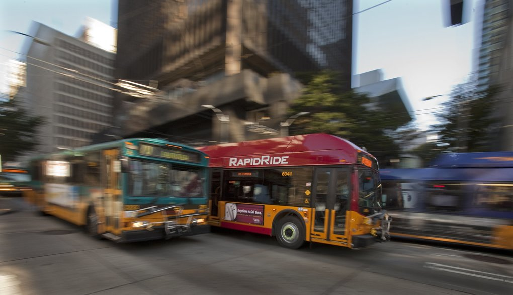 A new Rapid Ride bus route heading down 3rd Ave. in downtown Seattle sharing the road with other buses.