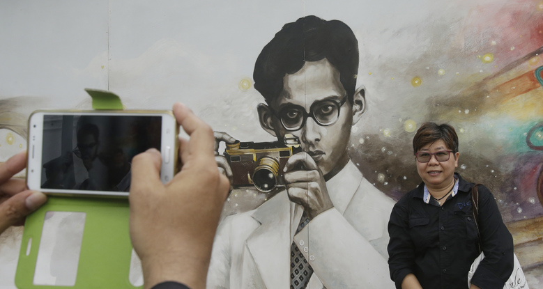 People take a picture of a drawing portrait of the late Thai King Bhumibol Adulyadej in Bangkok, Thailand, Tuesday, Oct. 18, 2016. Bhumibol was 8 when he got hold of his first camera – a Coronet Midget given by his mother – and rarely was one out of reach through most of his life, capturing both domestic scenes and documenting his efforts to improve rural lives. (AP Photo/Sakchai Lalit)