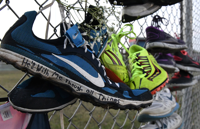 Pairs of track shoes are left on the fence at the entrance to a candlelight vigil for Trinity Gay at Lafayette High School, Monday, Oct. 17, 2016, in Lexington, Ky. Trinity Gay, the 15-year old daughter of Olympian and Lexington native Tyson Gay was shot and killed early Sunday morning. (AP Photo/Timothy D. Easley)