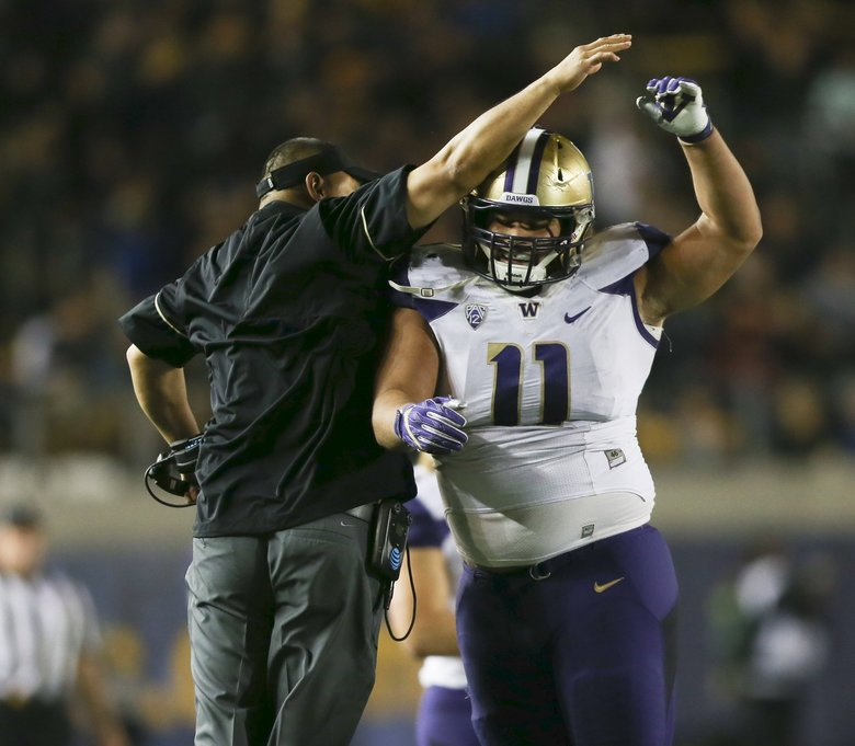 Washington Huskies defensive lineman Elijah Qualls (11) celebrates with defensive line coach Ikaika Malloe after the defense forced fourth down in the third quarter of a 2016 game against Cal.  (Johnny Andrews / The Seattle Times)