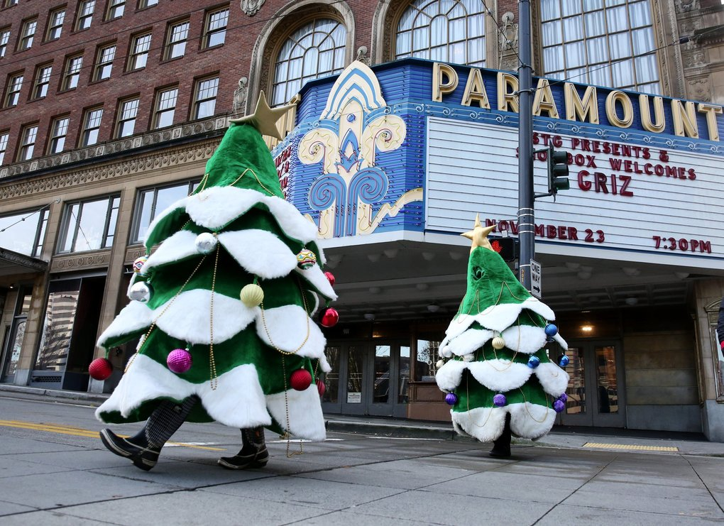Walking Christmas trees cross Pine Street in front of the Paramount Theatre to get into place before the start of the 26th annual My Macy's Holiday Parade on  Friday in downtown Seattle.  (Ken Lambert / The Seattle Times)