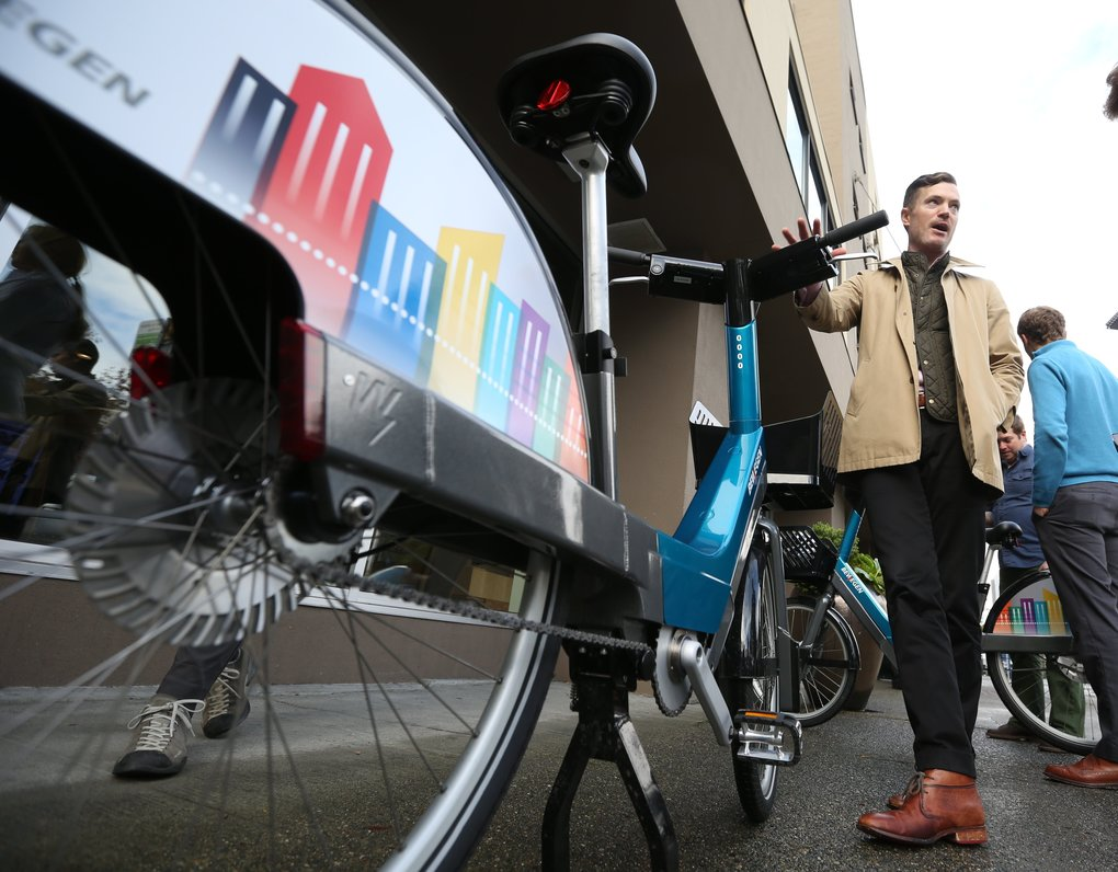 SDOT's Andrew Glass Hastings touts the features of the electric bike, part of the city's (Ken Lambert/The Seattle Times)