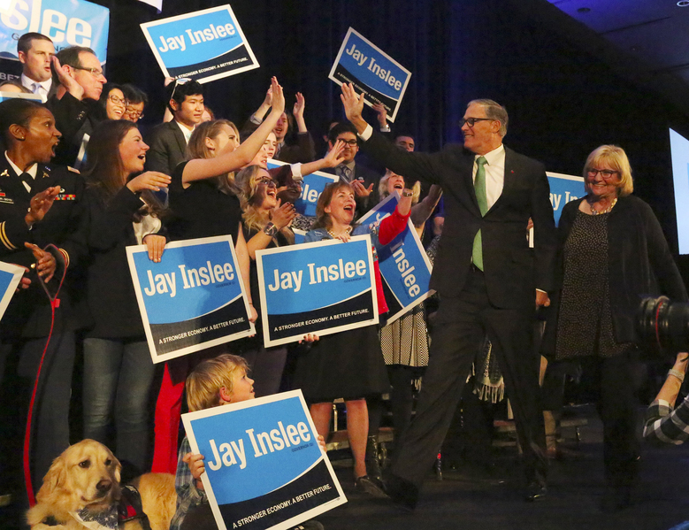 Gov. Jay Inslee, with wife Trudi at his side, walks on stage Tuesday evening to speak at a victory party in Seattle after securing re-election.  (Ken Lambert/The Seattle Times)