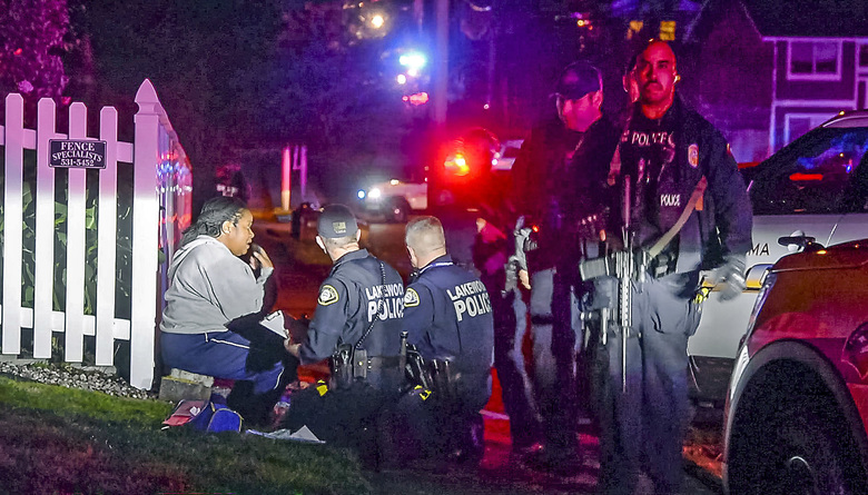Police gather near a  woman after a Tacoma police officer was shot while responding to a domestic-violence call Wednesday night. (Peter Haley / The News Tribune)