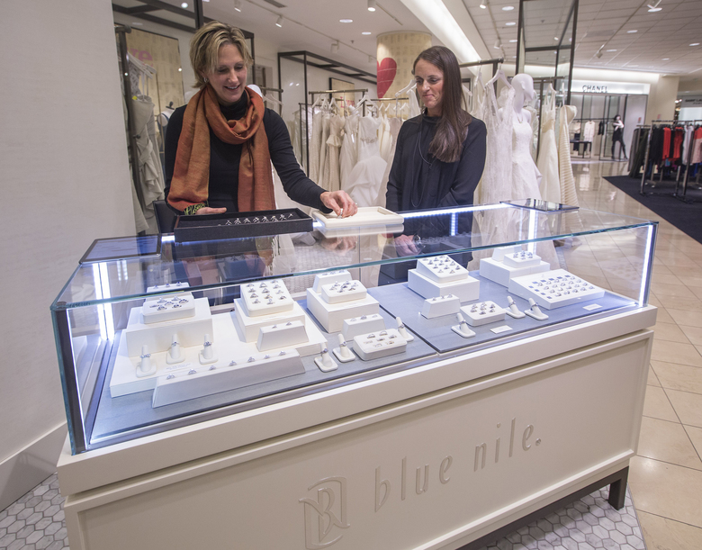 Blue Nile's Julie Yoakum, left, and Nordstrom's Shea Jensen at a display at Nordstrom's wedding studio.  (Steve Ringman/The Seattle Times)