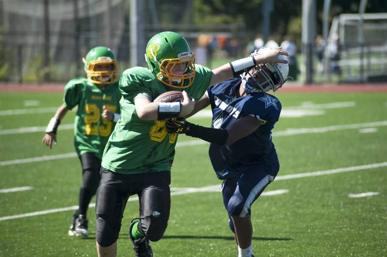 Sean Harmon, 11, carries the ball in a Brave Pride junior football game in 2014. He had recently received a heart screening.