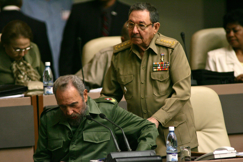 FILE – In this Dec. 23, 2004 file photo, Cuba's leader Fidel Castro, sitting, is helped into his chair by his brother Raul Castro as he arrives to the National Assembly in Havana, Cuba.  Former President Fidel Castro, who led a rebel army to improbable victory in Cuba, embraced Soviet-style communism and defied the power of 10 U.S. presidents during his half century rule, has died at age 90. The bearded revolutionary, who survived a crippling U.S. trade embargo as well as dozens, possibly hundreds, of assassination plots, died eight years after ill health forced him to formally hand power over to his younger brother Raul, who announced his death late Friday, Nov. 25, 2016, on state television. (AP Photo/Dario Lopez-Mills, File)