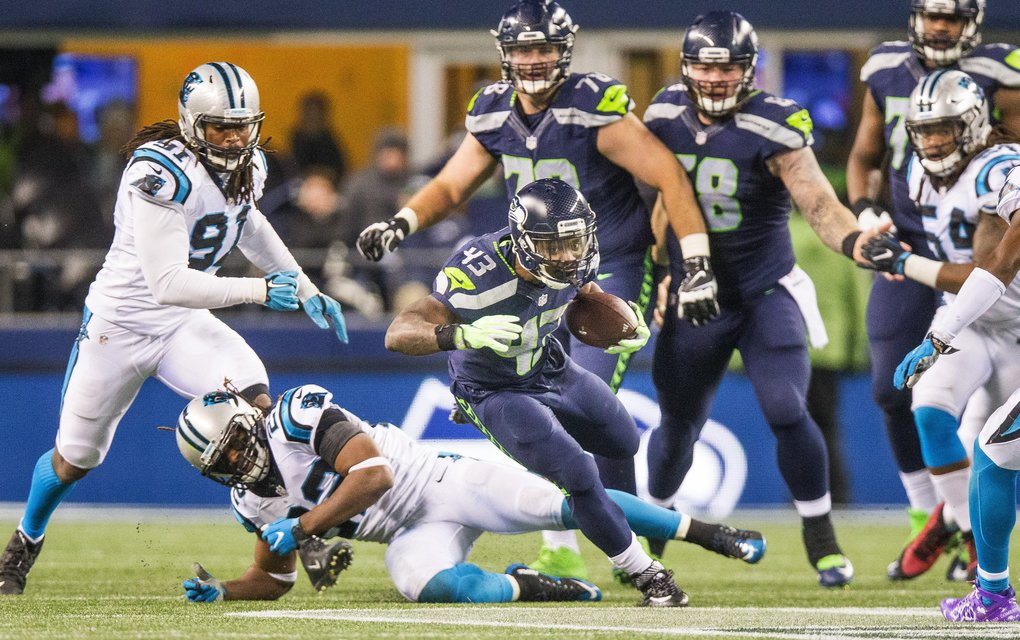 Seahawks running back Troymaine Pope breaks the grip of Carolina safety Michael Griffin and gallops for an 18 yard gain in the fourth quarter. (Dean Rutz / The Seattle Times)