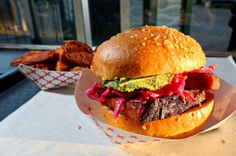 At Mean Sandwich in Ballard, the namesake has thick-cut corned beef, pickled red cabbage, yellow mustard, mint and maple syrup.  To the left is a plate of Skins & Ins — their version of fries — fried potato chunks and skins.  (Greg Gilbert / The Seattle Times)