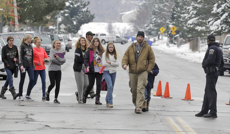 A police officer escorts students down the street following a school lockdown at Mueller Park Junior High after a student fired a gun into the ceiling Thursday, Dec. 1, 2016, in Bountiful, Utah. Police said two fast-acting Utah parents disarmed their son in the hallway of the Utah junior high school Thursday after the teenager brought the family's shotgun and handgun to school, discharging at least one round without injuring anyone. (AP Photo/Rick Bowmer)