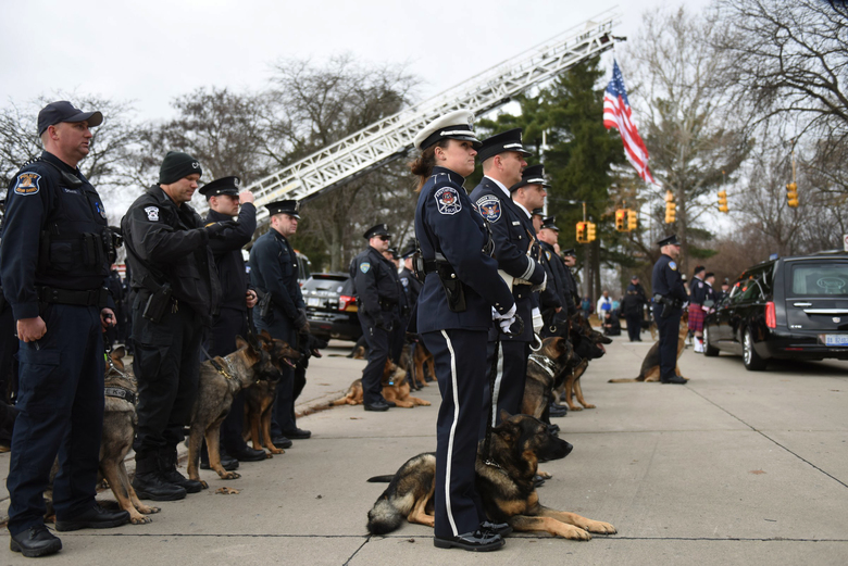K-9 and their police officer handlers from around the state line up to pay their final respects at the funeral of fallen Wayne State University Police officer Collin Rose held at St. Joan of Arc Catholic Church in St. Clair Shores Thursday, Dec. 1, 2016. Rose was shot Nov. 22 as he tried to arrest DeAngelo Davis, who faces murder and gun charges. (Tanya Moutzalias /The Ann Arbor News via AP)