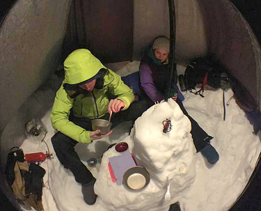 A lightweight tarp is an extra bit of snow-camping luxury that provides shelter from the elements and makes it easier to stay up and socialize when temperatures drop at night. (Photo courtesy of Erik Gates)