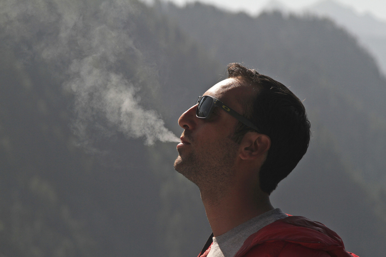"""In this Friday, Oct. 7, 2016 photo, French filmmaker Florent Dupont, 32, smokes a joint at a guesthouse in Malana village in the northern Indian state of Himachal Pradesh. """"It's just become a destination for international cool people, stoners, hikers,"""" said Dupont, as he sipped tea and rolled a joint in a guesthouse. Nestled deep in the higher reaches of the Indian Himalayas, Malana has become one of the world's top stoner destinations, and a symbolical battleground for India's fight against 'charas,' the black and sticky hashish that has made the village famous. (AP Photo/Rishabh R. Jain)"""